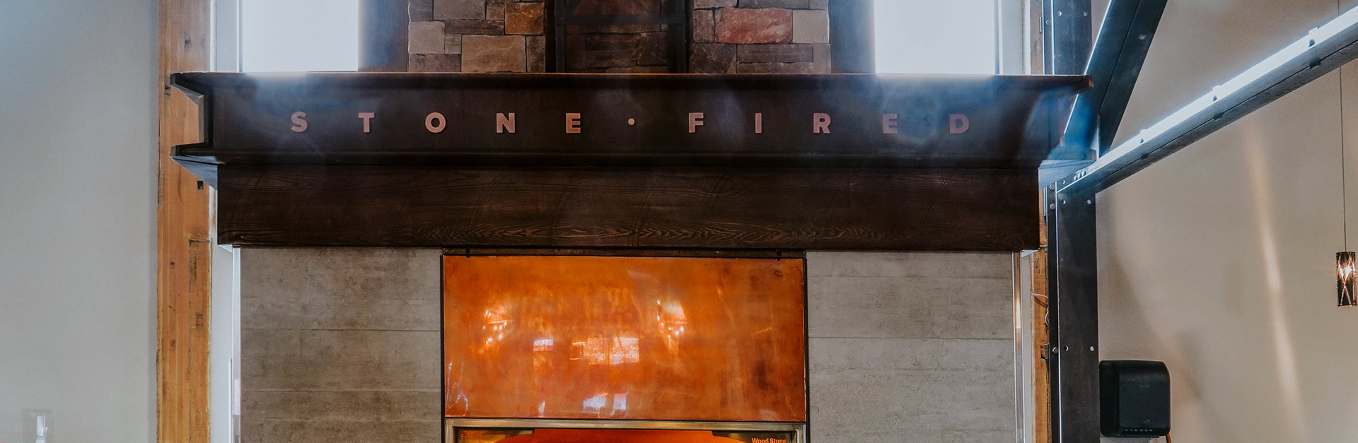 Stone Fired Pizza sign over a blazing stone oven